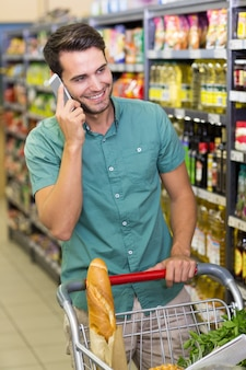 Smiling man buy food and phoning