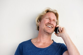 Smiling man by white wall and making phone call