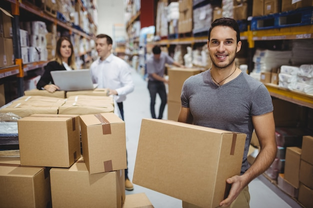 Smiling man carrying box in the warehouse
