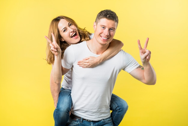 Smiling man carrying her girlfriend piggyback ride making victory sign