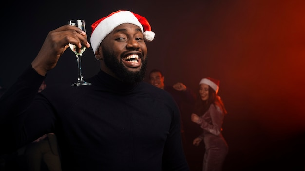 Smiling man cheering with champagne glass for new years