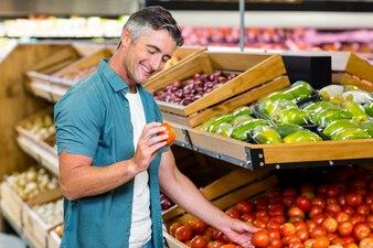 Smiling man choosing a tomato at supermarket