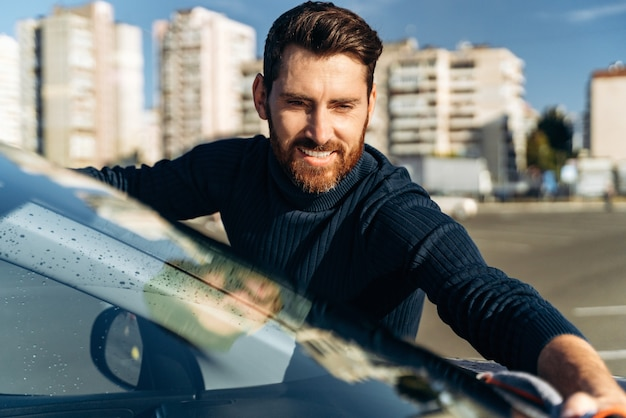 미소 짓는 남자가 차를 청소하고 극세사 천으로 차량을 건조합니다. 광택 후 광택이 나는 자동차의 페인트 표면을 손으로 닦아냅니다. 자동차 디테일링 및 세차 개념