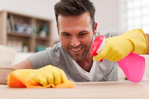 リビングルームの机を掃除する男の笑顔