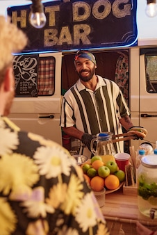 Smiling man cooking hot dogs in special van outdoors for people at a party