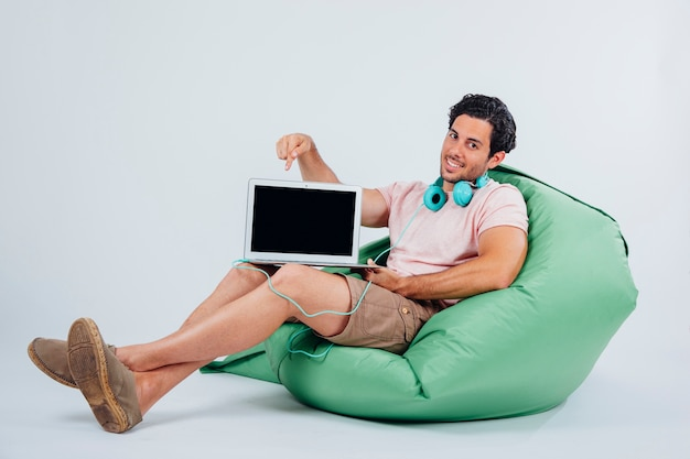 Smiling man on couch showing laptop