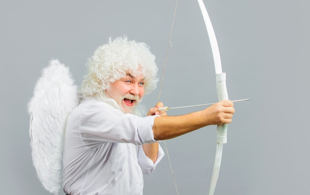 Smiling man in cupid costume on grey background.
