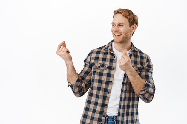 Smiling man dancing and snap fingers and having fun, dance and look happy, turn head aside at logo promotional text, standing over white wall