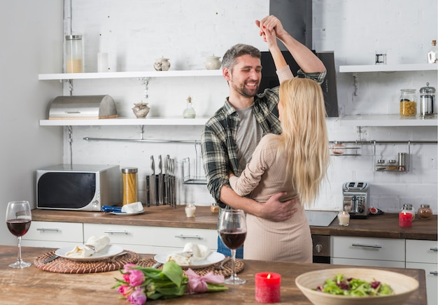 Smiling man dancing with blond woman near table in kitchen
