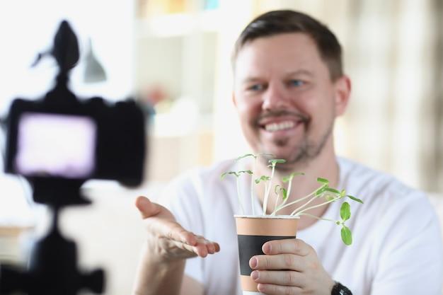 笑顔の男がビデオカメラで苗を実演