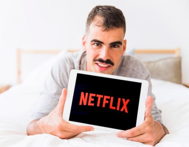 Smiling man demonstrating netflix logo in bedroom