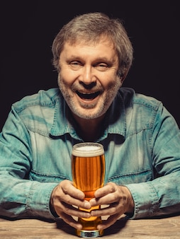 Smiling man in denim shirt with glass of beer