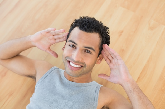 Smiling man doing abdominal crunches on parquet floor