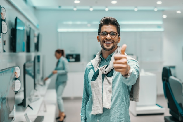 웃는 남자 우아하고 기술 상점에 서있는 동안 엄지 손가락을 포기하는 안경을 입고