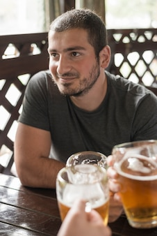 Smiling man drinking beer with friends at pub table