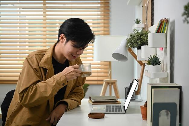 Улыбающийся человек пьет кофе и использует портативный компьютер.