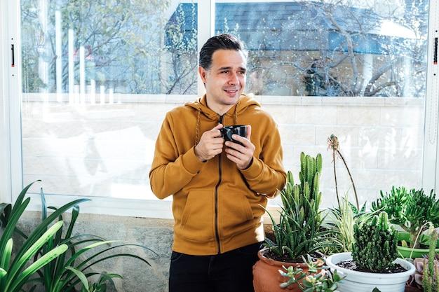 Улыбающийся человек пьет кофе у окна в окружении зеленых цветов и растений