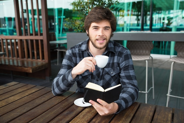 Smiling man drinking coffee and reading diary in street cafe
