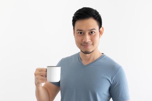 孤立した背景に笑顔の男がコーヒーを飲む