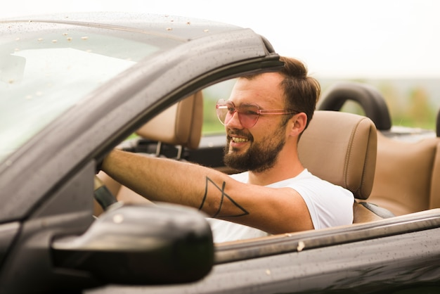 Smiling man driving a cabriolet