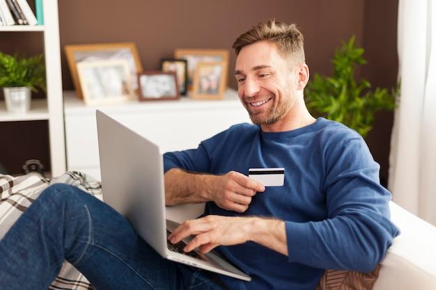 Улыбающийся человек во время покупок в интернете дома