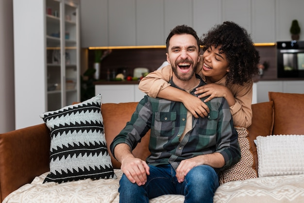 Smiling man embraced by his girlfriend