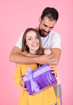 Smiling man embracing her girlfriend holding present against pink backdrop