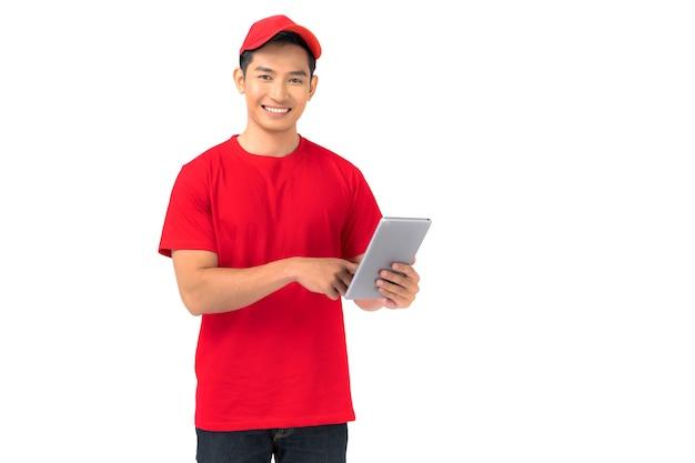 白で隔離のデジタルタブレットと立っている赤い帽子の空白のtシャツの制服を着た笑顔の男性従業員