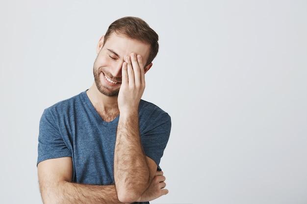 Улыбающийся человек лицевой маской после смущающей шутки