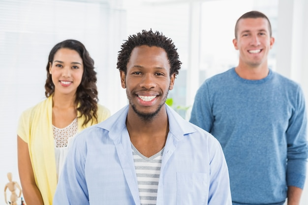 Smiling man in front of his colleagues looking at camera in the office