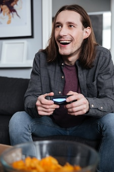 Smiling man gamer play games with joystick