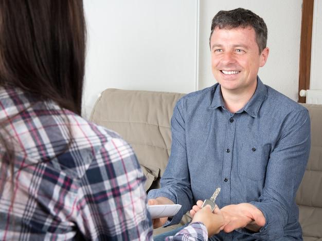 Улыбающийся человек получает ключи от новой квартиры после подписания документов