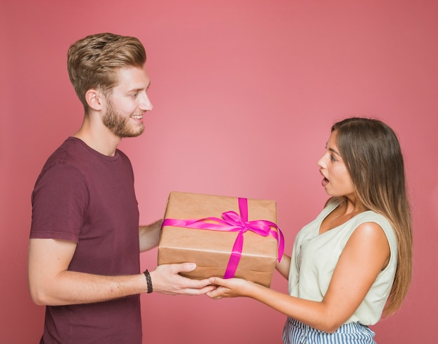 Smiling man giving gift box to her shocked girlfriend against colored background