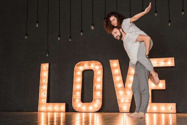 Smiling man giving her girlfriend piggyback ride standing in front of illuminated love text