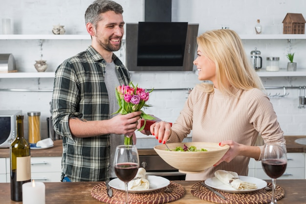 Smiling man giving present and flowers to cheerful woman with bowl in kitchen