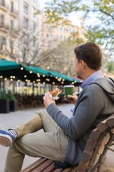 Улыбающийся человек обедает, сидя на скамейке