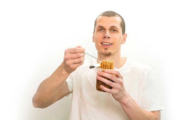 笑顔の男は、白い背景の上の透明なプラスチック製のカップにファーストフードの麺とフォークを保持します。