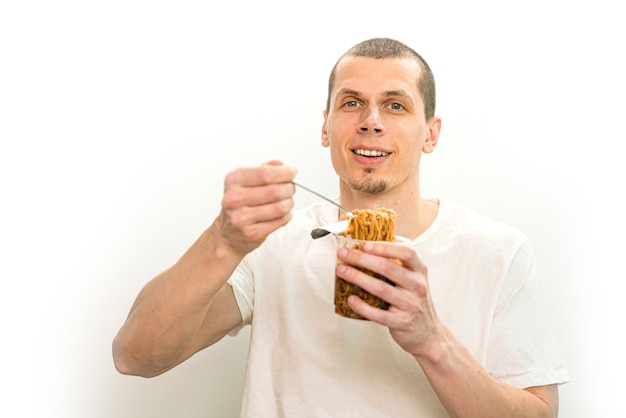 Smiling man hold a fork with fast food noodles in the transparent plastic cup on a white background.