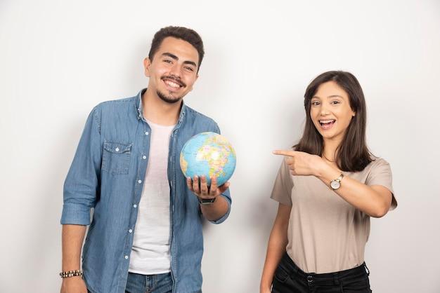 ポジティブな女の子の隣に地球儀を持っている笑顔の男。