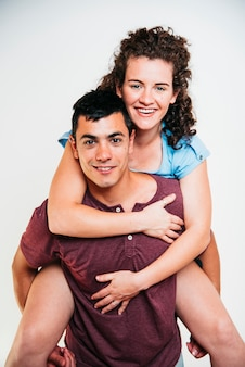 Smiling man holding on back young woman