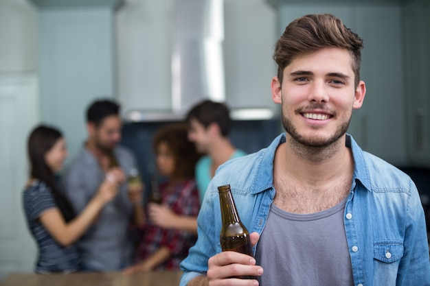 Smiling man holding beer bottle while friends
