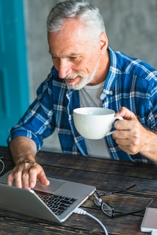 Smiling man holding coffee cup using laptop over the wooden desk