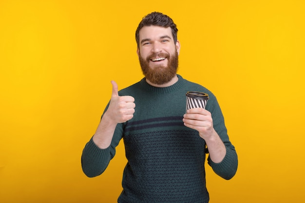 Smiling man holding cup of coffee to go and showing thumbs up