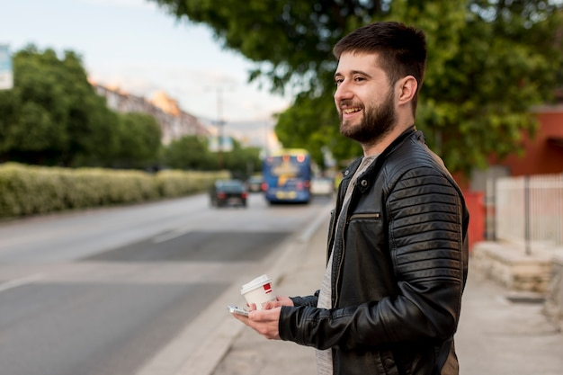 Smiling man holding cup and smartphone