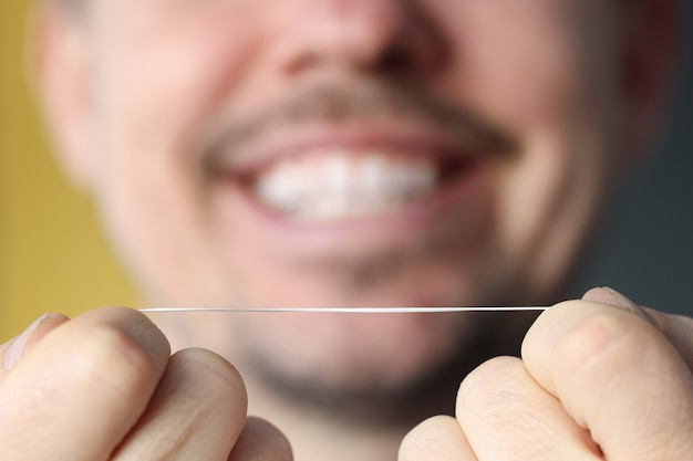Smiling man holding dental floss in his hands