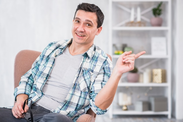 Smiling man holding eyeglasses and pointing away on chair at home