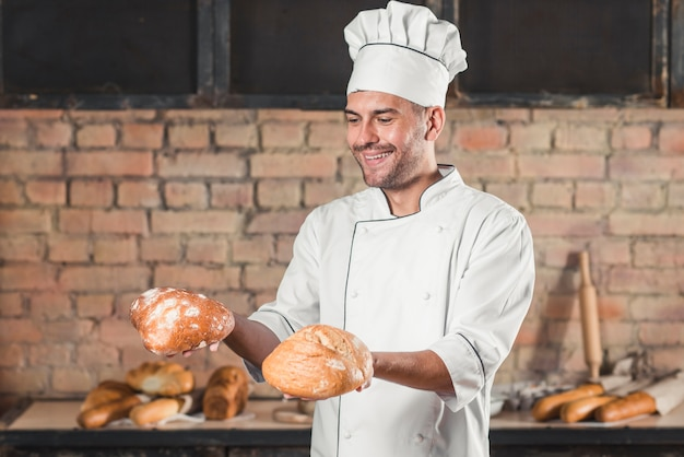 Smiling man holding fresh baked bread buns in hands