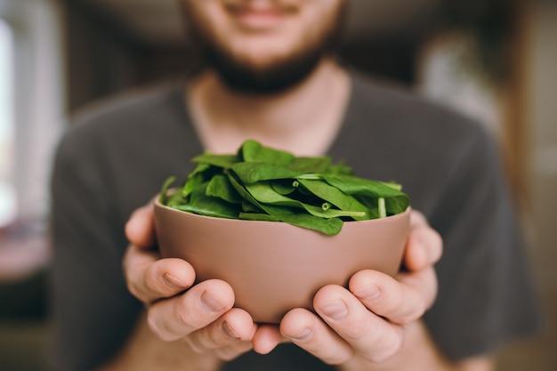 Улыбающийся человек держит свежий зеленый салат, листья шпината