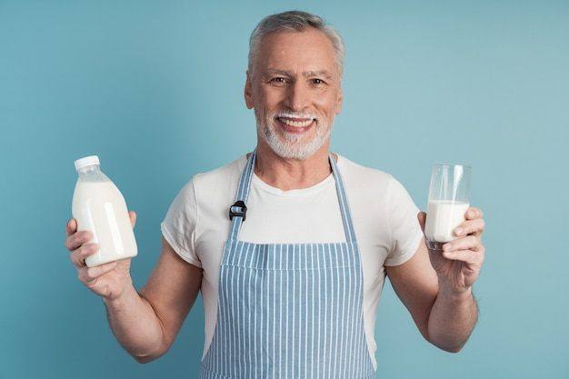 Smiling man holding a glass of milk and a bottle