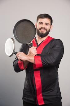 Улыбающийся человек держит в руках две темные сковороды.